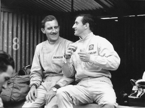 27 Jun 1965, Clermont-Ferrand, France --- Graham Hill (left) and Jackie Stewart, both drivers for BRM, sit and talk in the pit stop at the French Grand Prix in Clermont-Ferrand. --- Image by © Schlegelmilch/Corbis